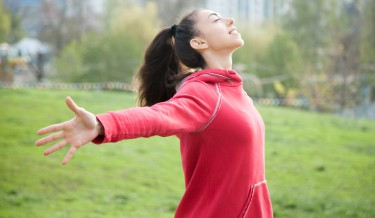 Profile portrait of happy sporty woman relaxing in park. Joyful female model relaxing, breathing fresh air outdoors with opened arms. Healthy active lifestyle concept